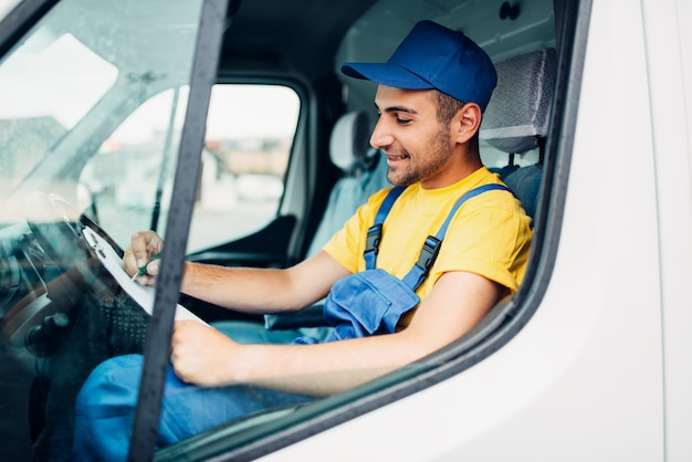 Cargo delivery service, male driver courier in uniform sitting in cab of truck. distribution business