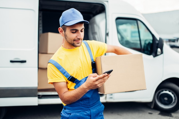 Cargo distribution industry, delivery service. worker in uniform with box and mobile phone in hands. empty container