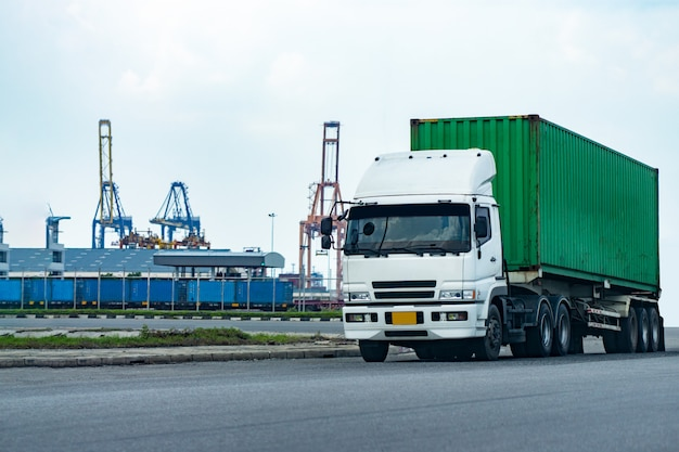 Cargo green container truck in ship port logistics.transportation industry in port business concept.