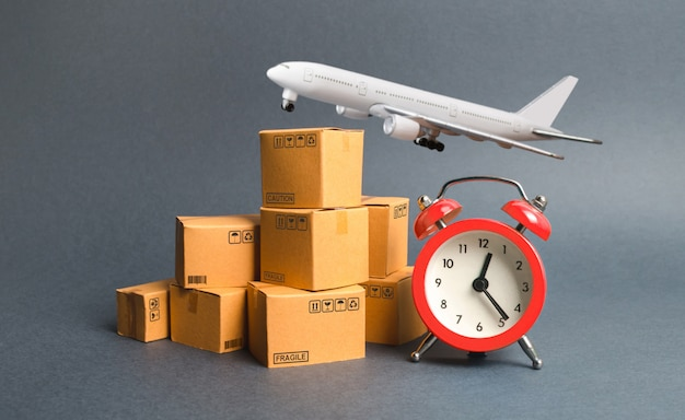 Cargo plane, stack of cardboard boxes and a red alarm clock. express air delivery concept