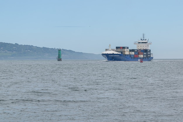 Cargo ship entering dublin harbour at poolbeg lighthouse from irish see.