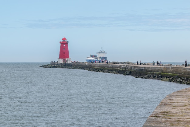 Cargo ship entering dublin harbour at poolbeg lighthouse.