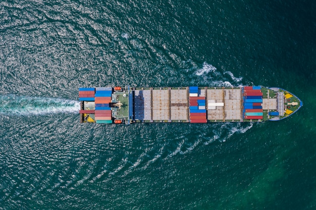 Cargo ship sailing on the sea top view from drone