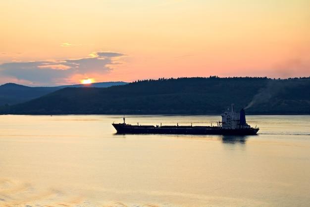 Cargo ship at the sunset mediterranean sea Premium Photo