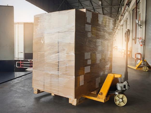 화물 배송 상자. 선적 컨테이너 트럭에 적재하는 골판지 상자 스택이있는 핸드 팔레트 잭.