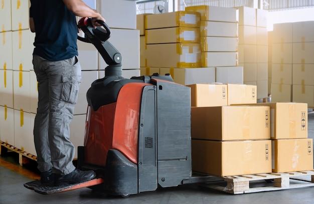 貨物輸送ボックス、倉庫保管。パレット上の段ボール箱を降ろす電動フォークリフトパレットジャッキで作業する労働者。