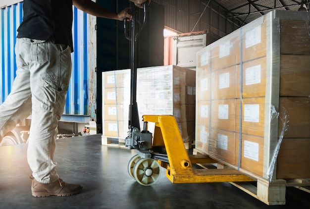 貨物輸送、倉庫保管、倉庫で貨物パレットを降ろすハンドパレットトラックで作業する労働者。