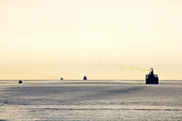 Cargo ships and boats at sunset