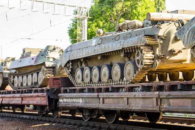 Cargo train carrying military tanks on railway flat wagons