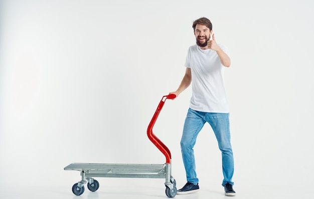 Cargo trolley man in jeans and sneakers light space work transportation