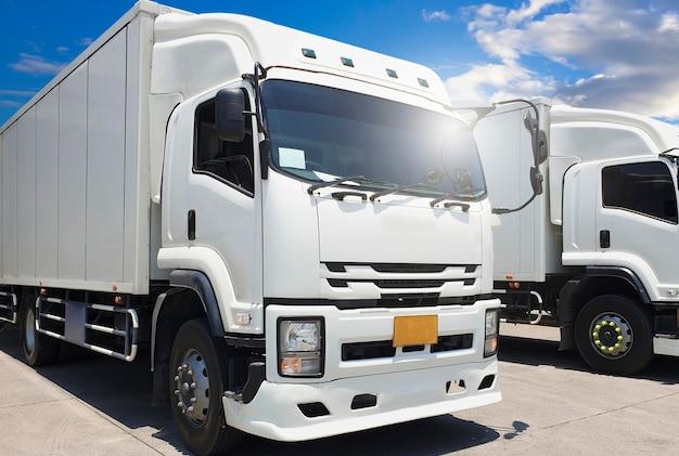 Грузовые автомобили на стоянке в blue sky industry. логистика и перевозки грузовых автомобилей.