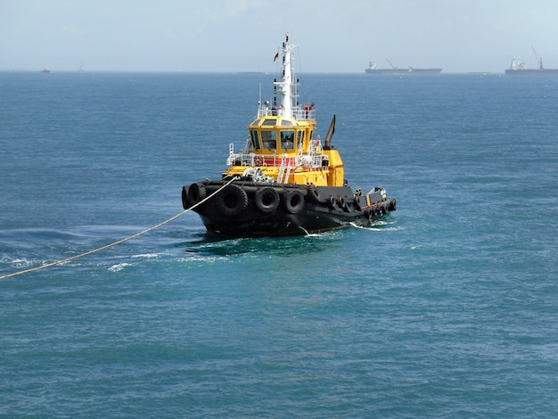 Cargo tug in the ocean pulls the ship into port