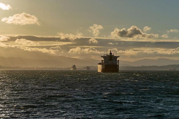 夕暮れ時の海で貨物船。物流のインポートおよびエクスポート事業。