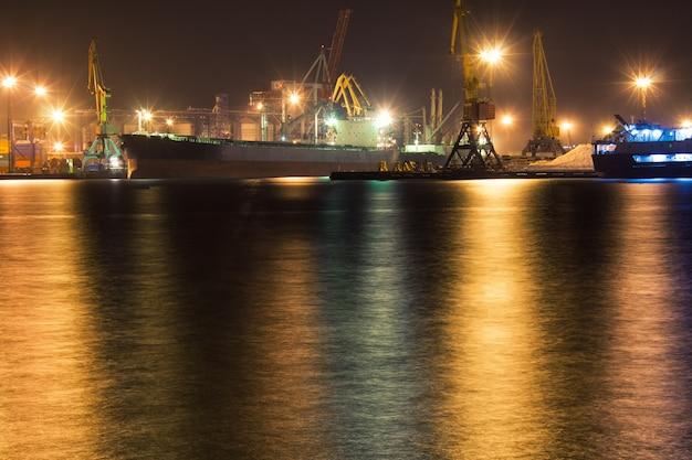 화물선은 크레인 조명 야경 사진과 함께 항구의 컨테이너 터미널에 정박되어 있습니다