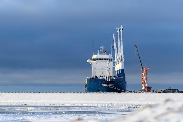 Cargo vessel moored in arctic port winter time ice navigation loading in progress