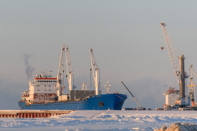 Грузовое судно пришвартовано в арктическом порту. зимнее время. ледовое плавание. идет погрузка.