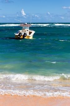 Карибский пляж с лодкой на море летом