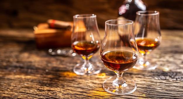 ラム酒のボトルと葉巻を背景にしたモダンなグラスのカリブ海のラム酒。