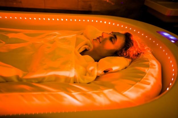 미용실, 바디 랩, 스파 살롱의 핫 스파 캡슐에 대한 배려. 열 담요로 덮여 특별한 스파 침대에 누워있는 젊은 여자