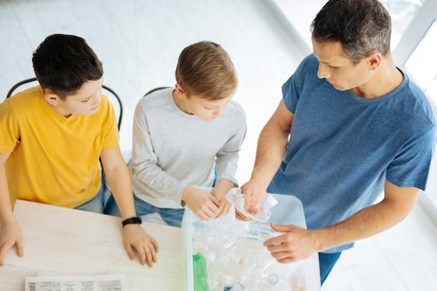 환경에 대한 배려. 잘 생긴 젊은 남자와 그의 10 대 전 아들이 플라스틱 병을 부수고 재활용을 위해 용기에 넣는 모습