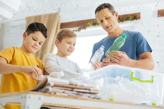 자연에 대한 배려. 재활용을 위해 플라스틱 병을 준비하고 병을 부수고 특수 용기에 넣는 매력적인 청년과 그의 십대 전 아들