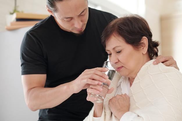 Заботливый взрослый сын дает больной матери стакан пресной воды, когда навещает ее дома