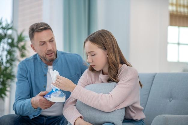 気配りの行き届いた父親、ナプキンを持っている悲しい娘を安心させ、両方ともソファに座っています。 Premium写真
