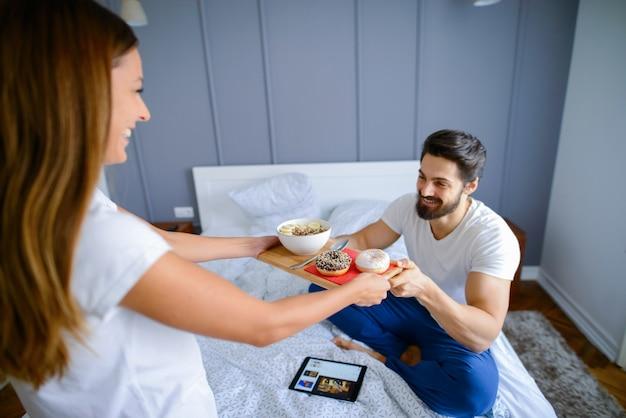 Заботливая милая девушка приносит завтрак своему парню в постель. пара голов.
