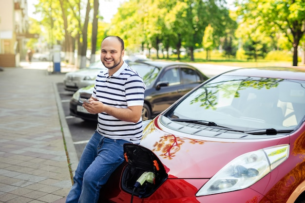Caring for the environment. a man connects a charger to an electric car in the city.