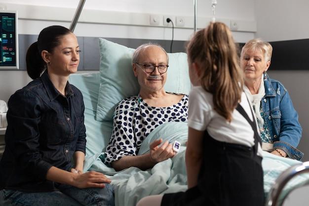 愛を示す年配の病気の祖父を訪問する思いやりのある家族