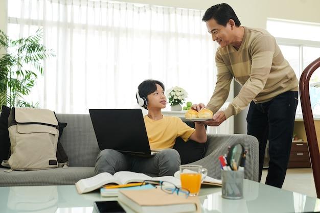 家でラップトップで宿題をしている彼の10代の息子に新鮮なパンとプレートを持って来る思いやりのある父