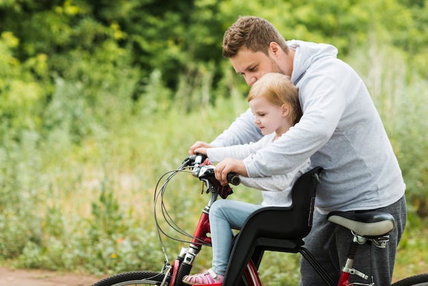Caring father holding daughter on bike
