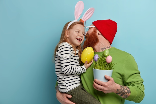Caring father kisses daughter and holds on hands, holds pot of decorated eggs, prepare for easter. happy ginger girl wears bunny ears, carries big yellow egg. religious holidays, celebration concept