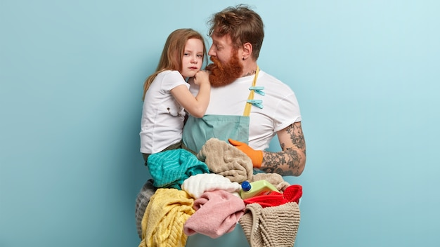 Caring father with thick bristle, red hair, tries to calm sorrowful crying small daughter, busy with housework, stands near basket full of laundry and detergent stands over blue wall. parenthood