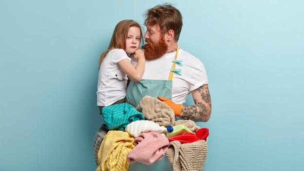 Padre premuroso con setole spesse, capelli rossi, cerca di calmare la piccola figlia piangente addolorata, impegnato con i lavori domestici, sta vicino a un cesto pieno di bucato e detersivo sopra il muro blu. genitorialità