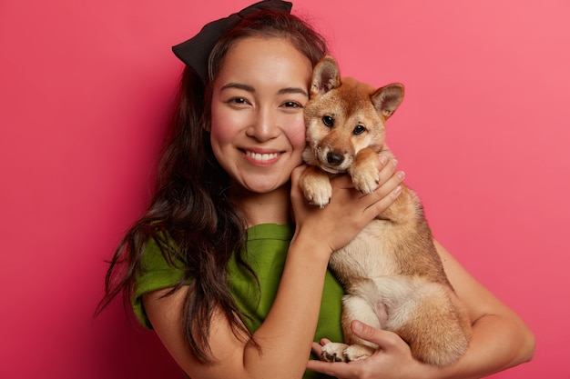 Caring female host poses with pedigree cute dog, glad to buy puppy, likes spending free time with domestic pet, expresses love