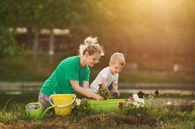 自然を気遣う。母と息子は川の土手に割り当ての地面に苗を植える。植物および生態学の概念。