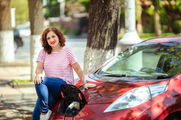 エコロジーと環境への配慮。女性は車にコレクター充電器を接続します。