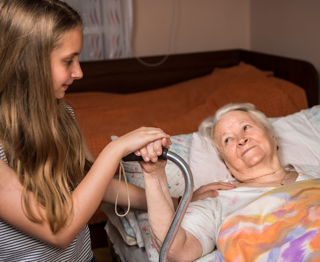 Caring girl holding old lady's hands in bed at home