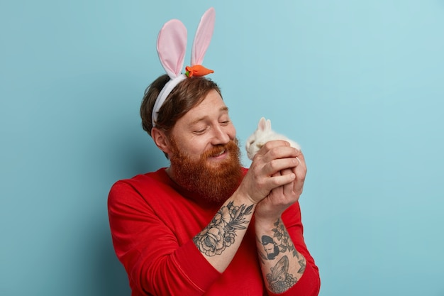 Caring glad ginger bearded man plays with little cute bunny, wears rabbit ears and red sweater, celebrates easter, enjoys spring time, poses indoor. traditions and religious holidays concept
