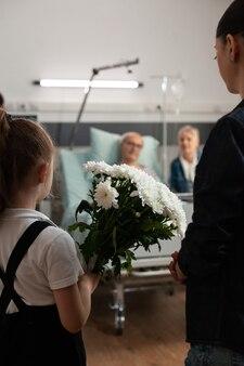病気の古い祖父に花の贈り物をもたらす思いやりのある孫娘