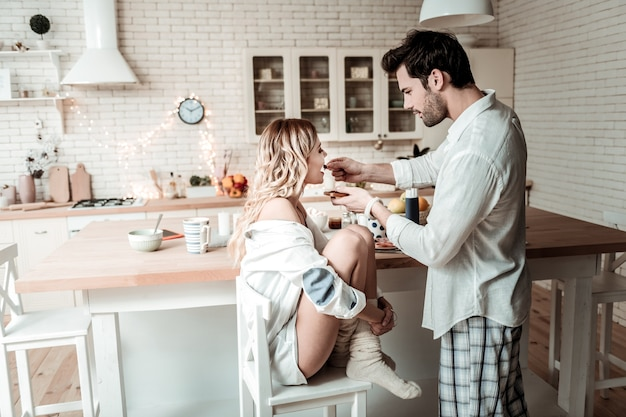 Caring husband. brunette bearded man in a white shirt feeling good while feeding his wife in the kitchen