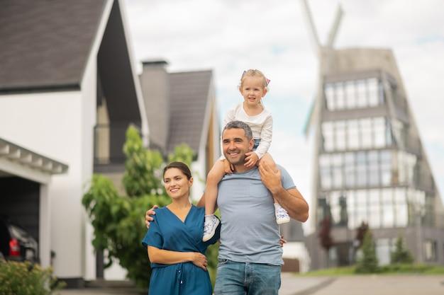 Заботливый муж. заботливый красивый муж обнимает жену и заботливая дочь на шее