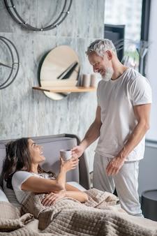 Заботливый муж. улыбающийся любящий седой мужчина в домашней одежде принес счастливой жене кофе в постели