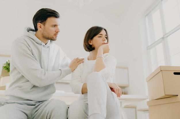 Заботливый муж пытается успокоить жену в трудной жизненной ситуации, переехать в новый дом для жизни, позировать в помещении возле картонных коробок, вместе решить домашние проблемы. женщина в стрессе, сталкивается с проблемой