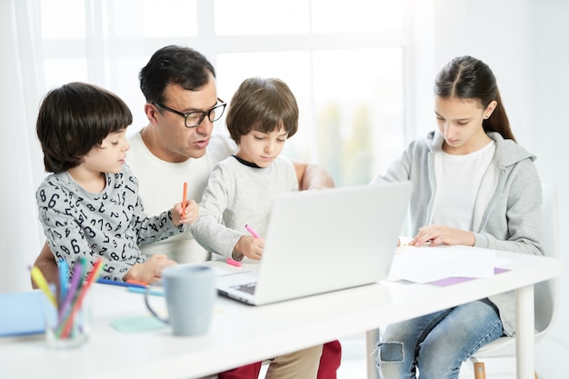 노트북을 사용하는 돌보는 라틴 아버지, 집에서 일하고 그와 함께 테이블에 앉아 있는 동안 아이들이 그림을 그리는 것을 지켜보세요. 프리랜서, 가족 개념