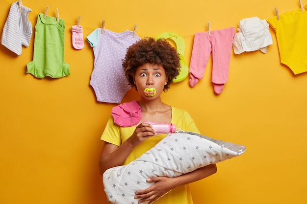 Caring loving mother keeps nipple in mouth, feeds baby with milk bottle, holds newborn on hands, busy with nursing and domestic chores, stands against yellow wall, has surprised expression