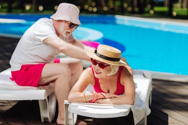 Заботливый любящий пенсионер делает массаж своей современной жене, лежа на шезлонге у бассейна