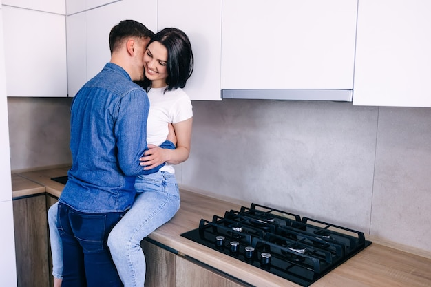 Caring married couple staying at home hugs together woman sitting at kitchen table