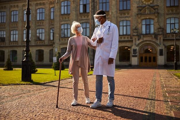 思いやりのある医療従事者が年配の女性を腕に抱き、散歩に出かける